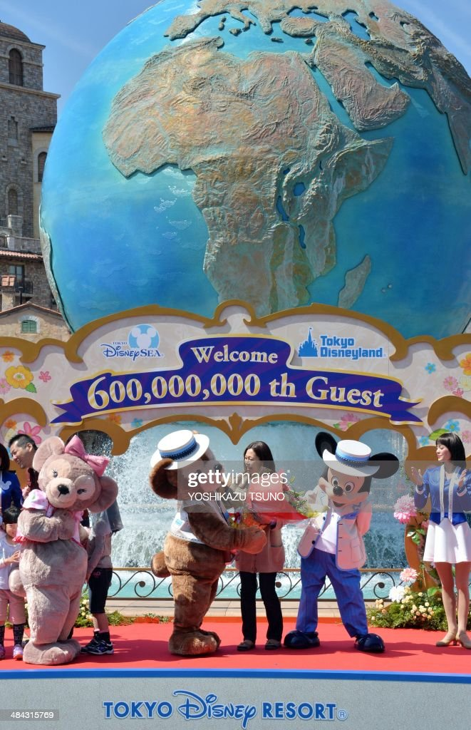 39-year-old nurse Yumi Sakai (C) celebrates with character Mickey Mouse (R) and Duffy (L) as she became Tokyo Disney Resort's 600,000,000 th guest at Tokyo DisneySea in Urayasu, suburban Tokyo on April 12, 2014. Japan's Disney theme parks, Tokyo Disneyland and Tokyo DisneySea, received its 600 millionth guest since its opening on April 15, 1983 and September 4, 2001. The parks logged a record high of 31 million visitors in fiscal 2013 year ended March 31 as the Tokyo Disneyland commemorated its 30th anniversary last year. AFP PHOTO / Yoshikazu TSUNO