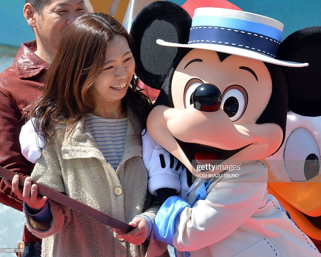 39-year-old nurse Yumi Sakai (L) celebrates with character Mickey Mouse (R) as she became Tokyo Disney Resort's 600,000,000 th guest at the Tokyo DisneySea in Urayasu, suburban Tokyo on April 12, 2014. Japan's Disney theme parks, Tokyo Disneyland and Tokyo DisneySea, received its 600 millionth guest since its opening on April 15, 1983 and September 4, 2001. The parks logged a record high of 31 million visitors in fiscal 2013 year ended March 31 as the Tokyo Disneyland commemorated its 30th anniversary last year. AFP PHOTO / Yoshikazu TSUNO