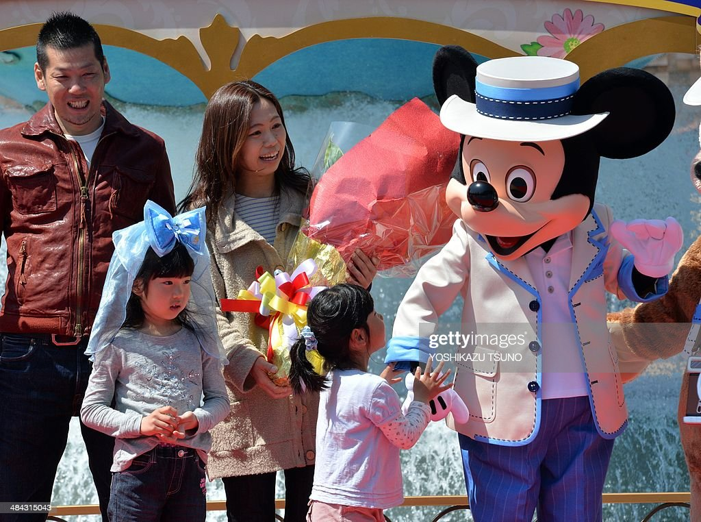 39-year-old nurse Yumi Sakai (back 2nd L) celebrates with her family and characters as she became Tokyo Disney Resort's 600,000,000 th guest at the Tokyo DisneySea in Urayasu, suburban Tokyo on April 12, 2014. Japan's Disney theme parks, Tokyo Disneyland and Tokyo DisneySea, received its 600 millionth guest since its opening on April 15, 1983 and September 4, 2001. The parks logged a record high of 31 million visitors in fiscal 2013 year ended March 31 as the Tokyo Disneyland commemorated its 30th anniversary last year. AFP PHOTO / Yoshikazu TSUNO