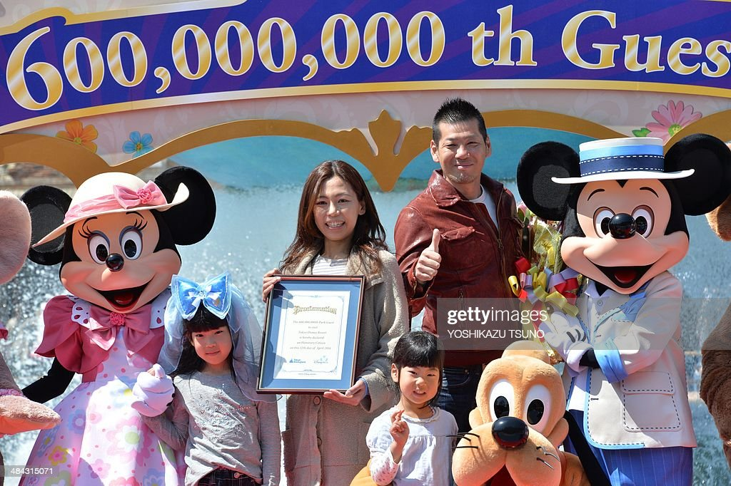 39-year-old nurse Yumi Sakai (C) celebrates with her family and characters as she became Tokyo Disney Resort's 600,000,000 th guest at the Tokyo DisneySea in Urayasu, suburban Tokyo on April 12, 2014. Japan's Disney theme parks, Tokyo Disneyland and Tokyo DisneySea, received its 600 millionth guest since its opening on April 15, 1983 and September 4, 2001. The parks logged a record high of 31 million visitors in fiscal 2013 year ended March 31 as the Tokyo Disneyland commemorated its 30th anniversary last year. AFP PHOTO / Yoshikazu TSUNO