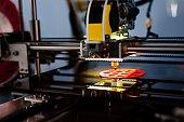 3d printer working and printing plastic prototype