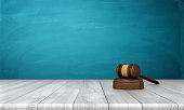 3d rendering of a brown wooden judge gavel and sound block lying on a wooden table with blue background. Judicial power. Domestic law. Legal advice.