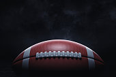 3d rendering of a leather ball for American football lying with its seams in focus on a dark background. American national game. American football gear. Ball for professional sport.