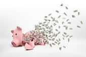 3d rendering of a pink broken piggy bank lying on a white background with many dollar banknotes flying out of it. Loss of savings. No more funds. Bankruptcy and crisis.