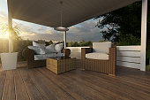 3d rendering of rattan garden furniture on wooden patio at garden in the evening sunshine