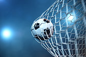 3d rendering soccer ball in goal. Soccer ball in net with spotlight or stadium light background. Success concept