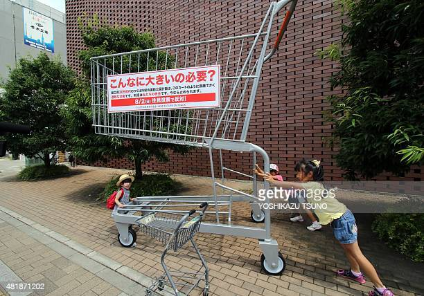A 3meter tall oversized shopping cart is displayed at a shopping mall in Tsukuba suburban Tokyo on July 25 2015 to protest against construction plan...