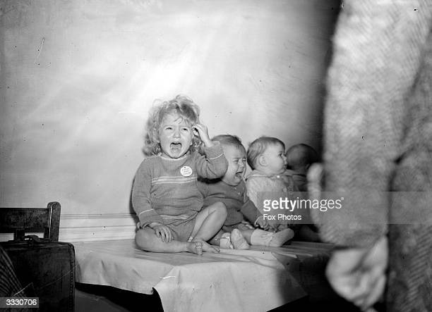 A little girl and a baby crying at the Old Oak Infant Centre Shepherd's Bush London On the orders of Hammersmith Borough Council infants at this...