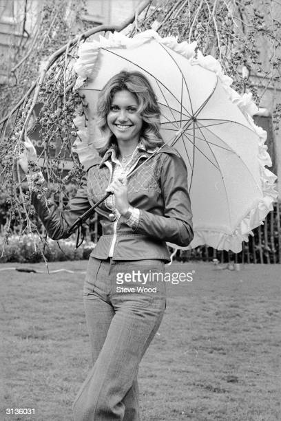British born Australian singer and actress Olivia NewtonJohn holding a parasol