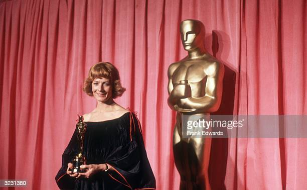 British actor Vanessa Redgrave stands in front of a red curtain and a large Oscar statue smiling and holding the Oscar she won for Best Supporting...