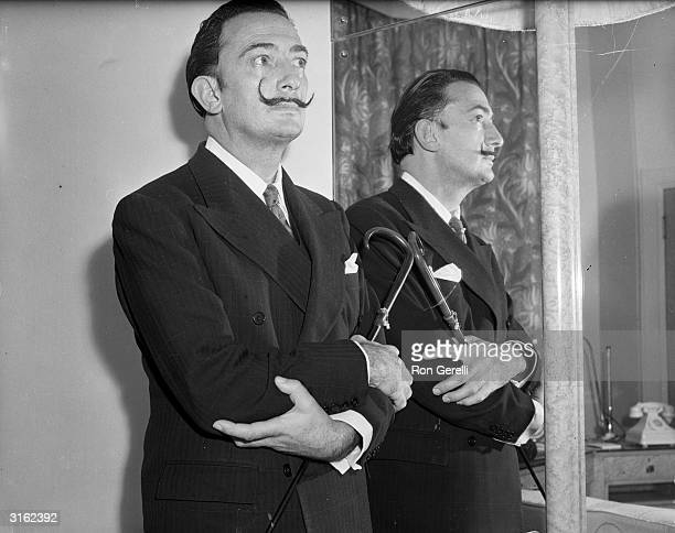 Spanish surrealist artist Salvador Dali next to a mirror
