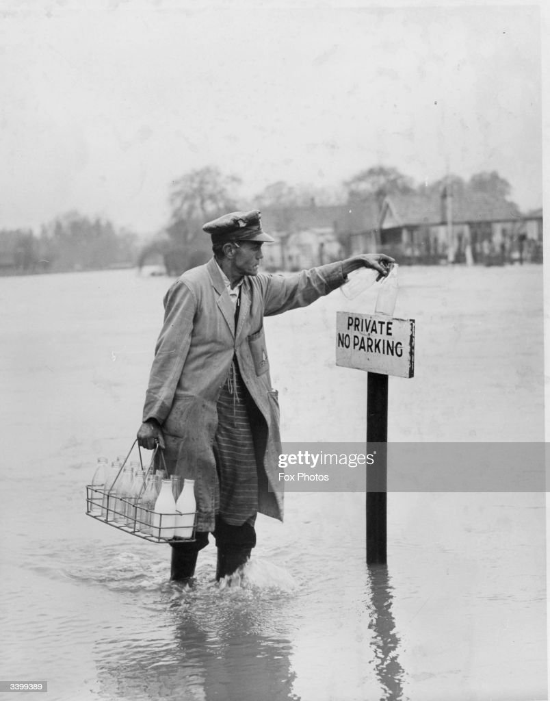 A sign saying 'Private No Parking' rises out of floodwater and provides a handy resting place for empty milkbottles being collected by milkman Bill Turner at Old Windsor, Buckinghamshire.