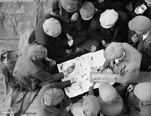 A group of British labourers playing a game of cards on a newspaper spread out on a tarpaulin