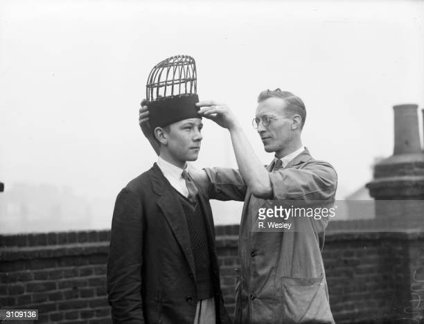 A worker at Robson's factory in Tooley Street London fits a cane structure on the head of a live model from which a busby of the Guardsman will be...