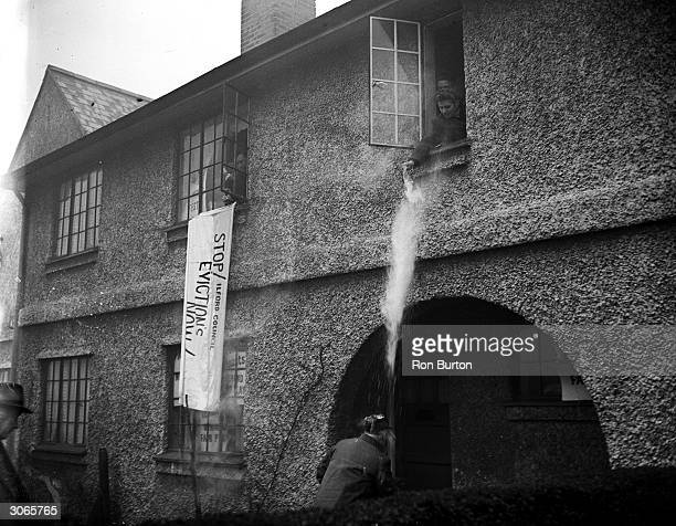 A bailiff is showered with hot water as he arrives to evict the tenants of Mr Arthur Colton's home in Fencepiece Road Ilford Essex but the show of...