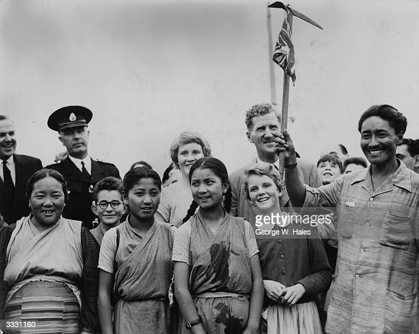 Sherpa Tensing waving an icepick with a Union Jack tied to it when he arrived at London Airport after his successful ascent of Everest Behind him is...