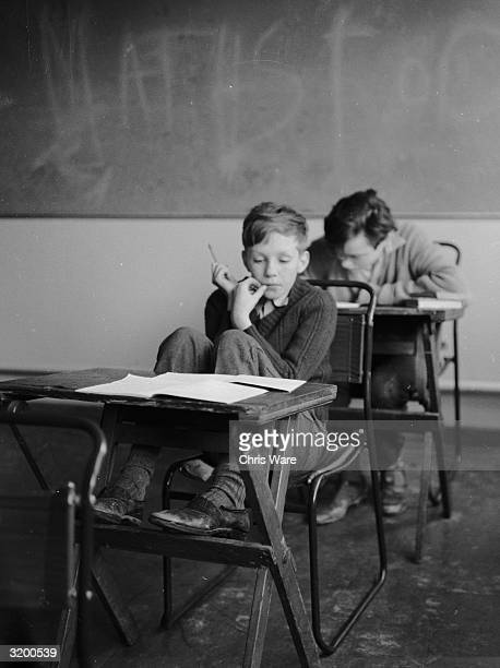 A pupil at Red Hill School Kent a grammar school for maladjusted boys with a nonpunitive approach is lost in thought over a lesson