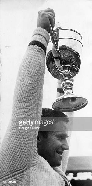Australian tennis player Roy Emerson lifts the men's singles trophy after defeating Fred Stolle at the Wimbledon Tennis Championships