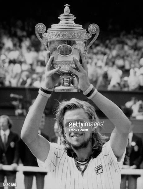 Twentyyearold Swedish tennis player Bjorn Borg holds aloft the Wimbledon Men's Singles trophy after beating Ilie Nastase of Romania 64 62 97