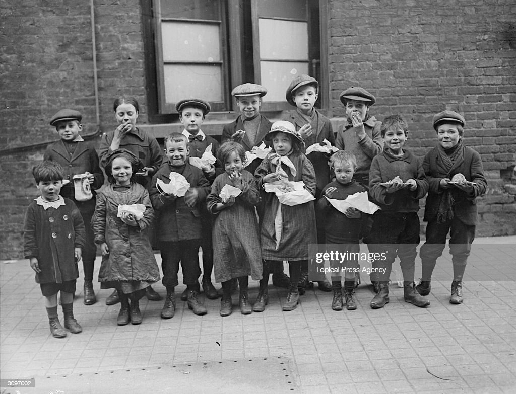 Children eating a penny's worth of Plum Duff from soup kitchens in Bermondsey, south London.