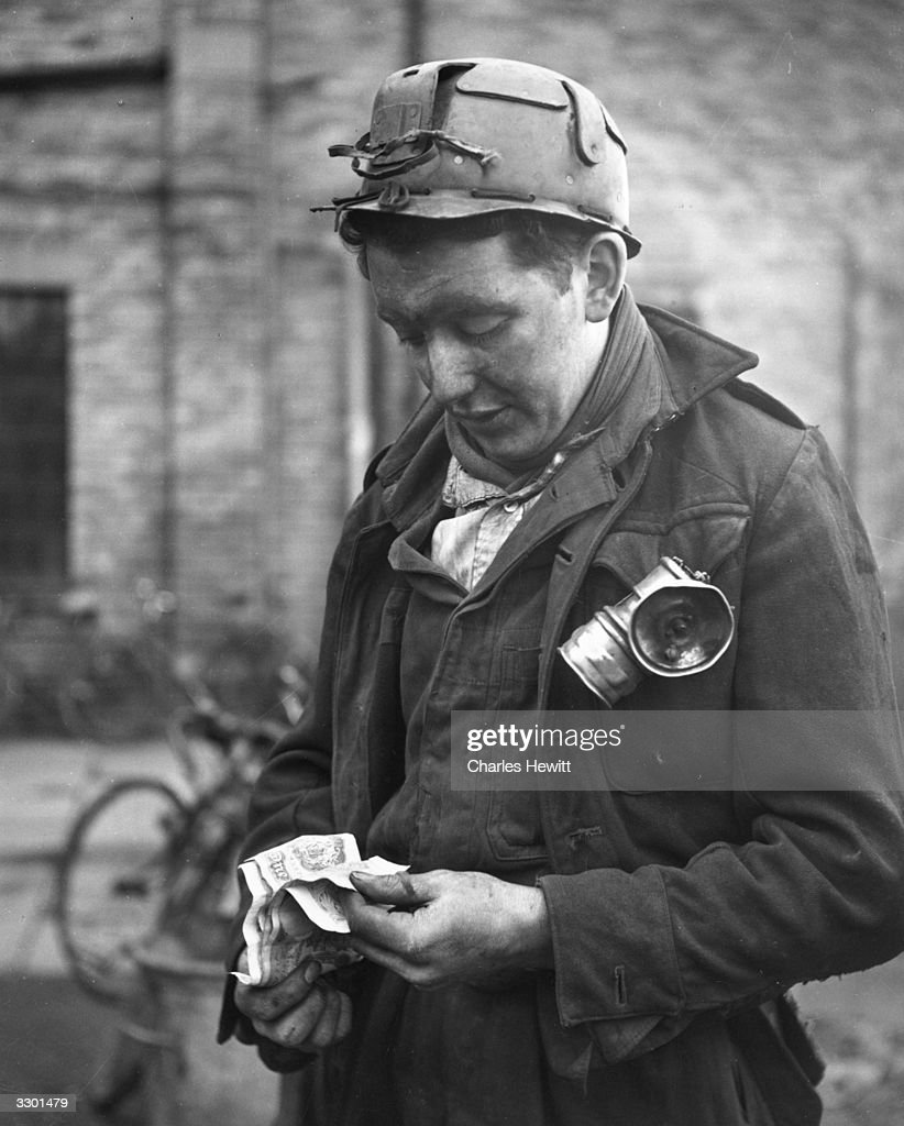 A young miner from Ellington Colliery, Northumberland, checks his money after attending a pay parade. Original Publication: Picture Post - 5215 - Why Another Coal Crisis? - pub. 1951