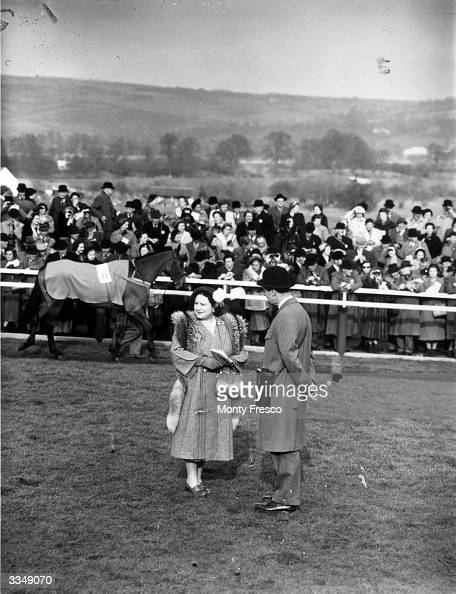 Queen Elizabeth The Queen Mother watching a parade for the National Hunt Steeplechase from within the enclosure at Cheltenham racecourse...