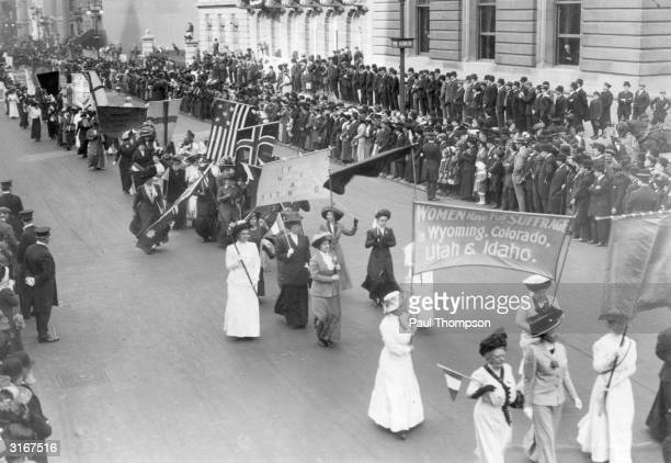 Suffragettes carrying a banner announcing that 'Women have full suffrage in Wyoming Colorado Utah and Idaho' at the Women of all Nations Parade in...