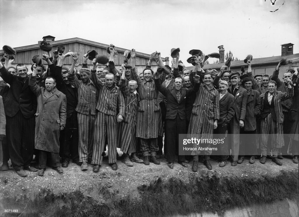 Liberated prisoners from Dachau, the German concentration camp wave in joy. Those wearing striped uniforms are political prisoners whose fate was cremation if they had not been liberted by the US 7th Army.