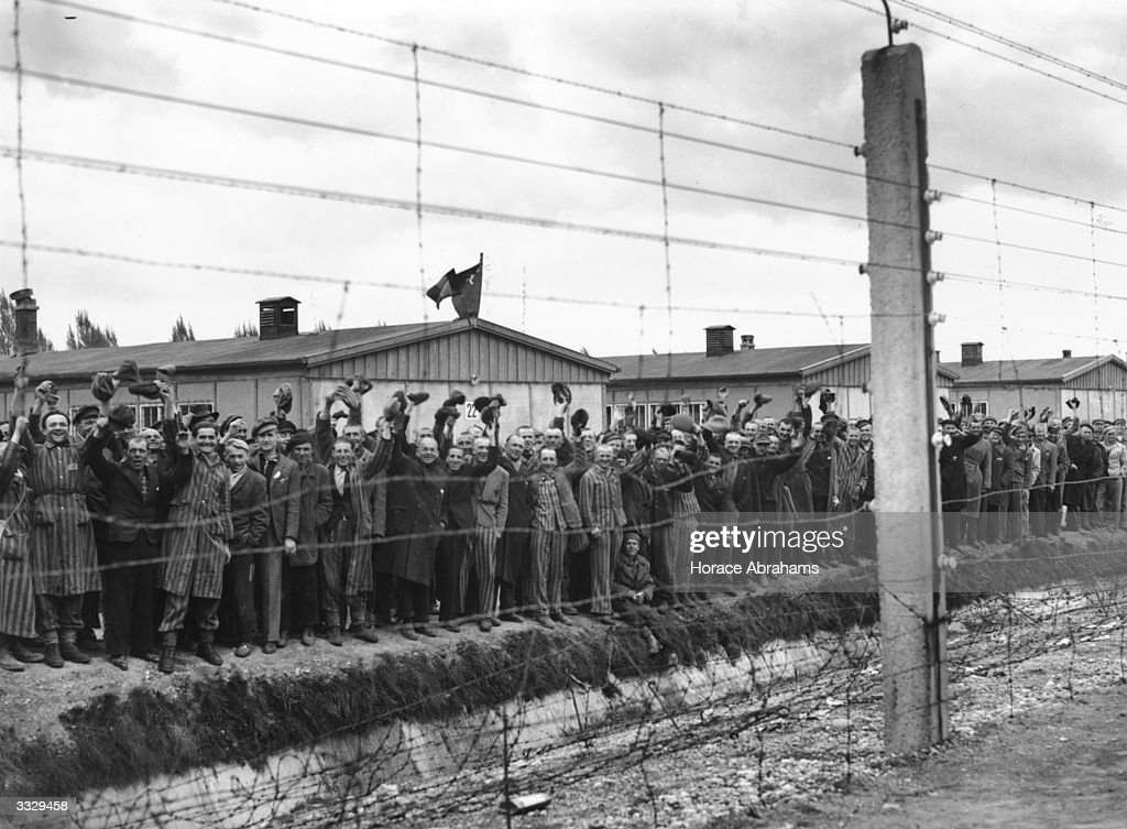 Prisoners behind the electric fence at Dachau concentration camp cheer the US troops who liberated the camp. Some of the prisoners are wearing striped prison uniforms.