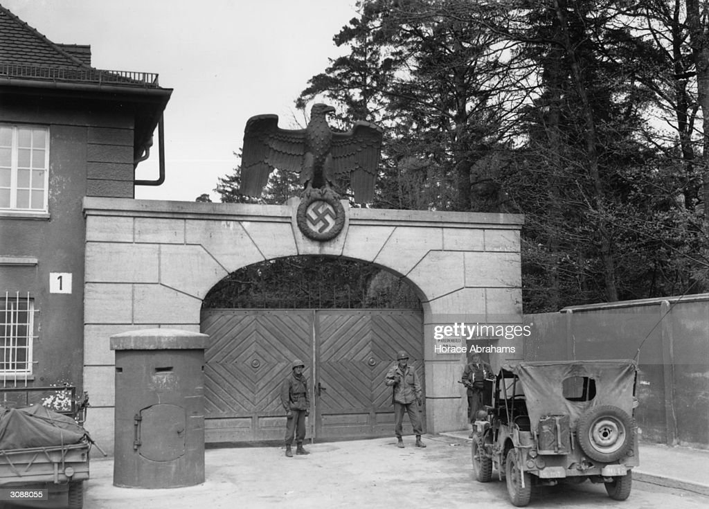 The main entrance to Dachau concentration camp. The German eagle and a swastika stand guard over the gate.