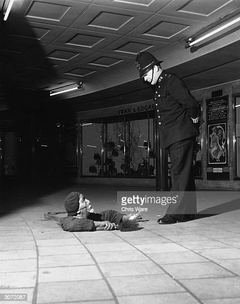 An Underground maintainance worker pops up through a manhole cover at the feet of a policeman at Piccadilly Tube Station