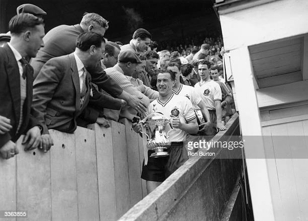 Supporters congratulate Bolton captain Nat Lofthouse as he leads his team down the steps with theFA Cup trophy after Bolton Wanbderers' 20 victory...
