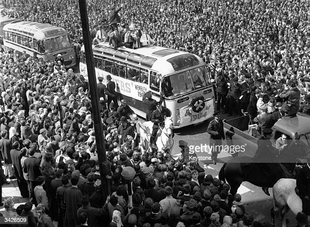 Members of the victorious West Ham team who beat Preston North End 32 riding on an open top bus to parade the FA Cup through crowds of fans in London