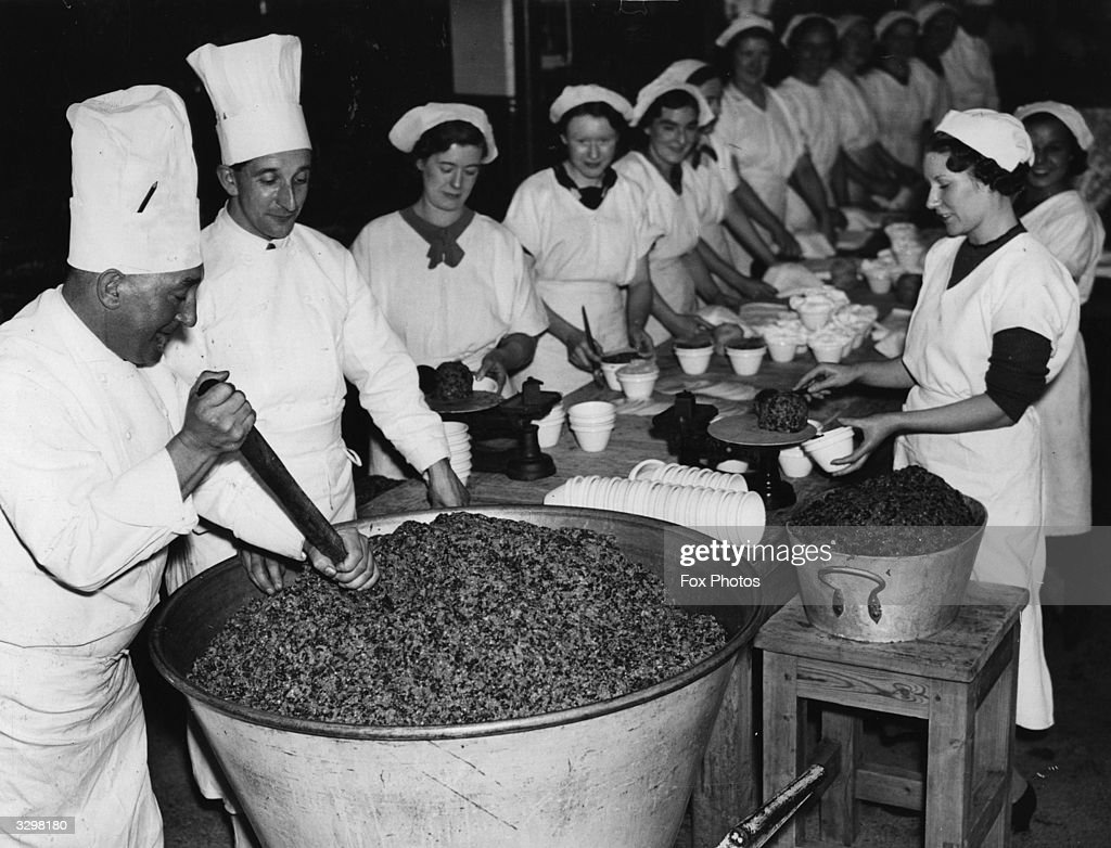 Cooks mixing Christmas pudding mixture at Crosse and Blackwell factory at Bermondsey in a huge container