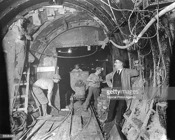 Men at work digging and bolting the outer tunnel showing the inner tunnel at Bethnal Green on the new East London London Underground extension