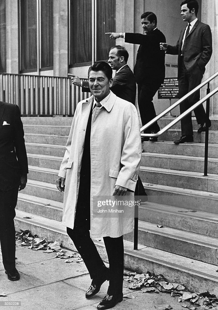 US statesman and former film actor Ronald Reagan, governor of California, leaves the US Embassy at Grosvenor Square, London. Behind him, security men point at demonstrators.