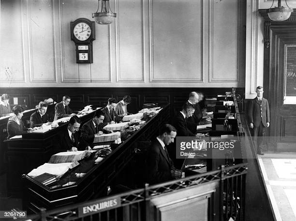 Rows of clerks at work making manual entries to the ledgers in the interior of a bank while a doorman stands by the door