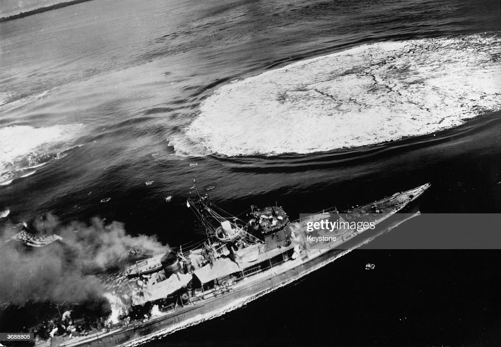 As a pool of foam from a near miss spreads out, smoke rises from a direct hit on a Japanese submarine chaser by bombers of the Fifth US Army Air Force. The vessel was part of a convoy en route to a nearby Japanese base when it was bombed in the waters off New Ireland in the southwest Pacific.