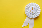 3rd place white ribbon rosette with gold text for the runner up in a competition or race on a yellow background with copy space