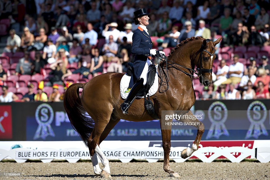 3rd placed Dutch rider <a gi-track='captionPersonalityLinkClicked' href=/galleries/search?phrase=Adelinde+Cornelissen&family=editorial&specificpeople=5427385 ng-click='$event.stopPropagation()'>Adelinde Cornelissen</a> on her horse Parzival celebrates after competing in the FEI Dressage European Championship Finals in Herning, Denmark, on August 25, 2013. British rider Charlotte Dujardin won the event followed by 2nd placed German rider Helen Langehanenberg and Cornelissen.