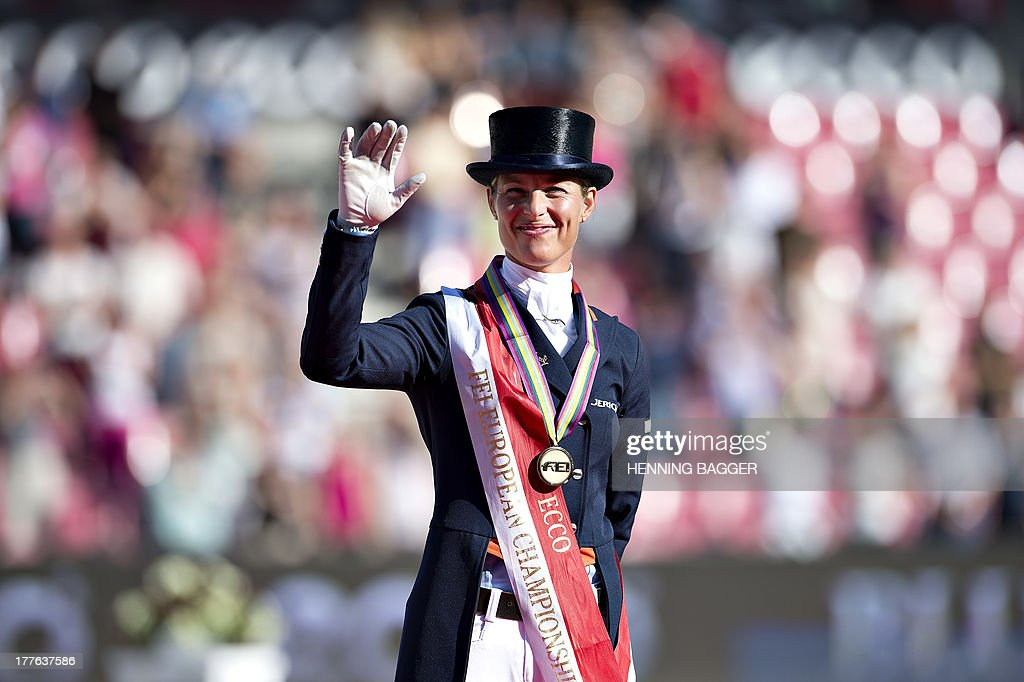 3rd placed Dutch rider <a gi-track='captionPersonalityLinkClicked' href=/galleries/search?phrase=Adelinde+Cornelissen&family=editorial&specificpeople=5427385 ng-click='$event.stopPropagation()'>Adelinde Cornelissen</a> poses on the podium after competing in the FEI Dressage European Championship Finals in Herning, Denmark, on August 25, 2013. British rider Charlotte Dujardin won the event followed by 2nd placed German rider Helen Langehanenberg and Cornelissen.