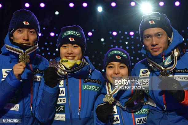 3rd placed Japanese team Daiki Ito Yuki Ito Sara Takanashi and Taku Takeuchi pose for photographers during the medals ceremony for ski jumping normal...