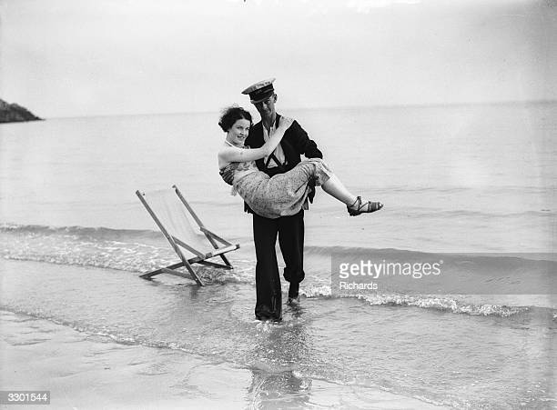 A young lady falls asleep on the beach and has to be rescued from the advancing tide by a gallant deckchair attendant at Barry Island South Wales