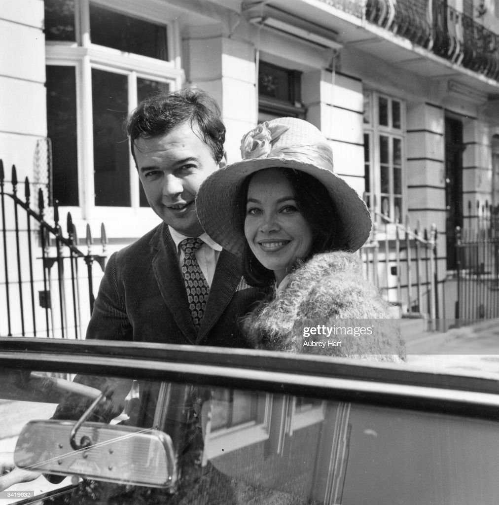 The English stage director and theatre manager, Sir Peter Hall (1930 - ) and his wife, the actress, Leslie Caron, setting off on holiday to Naples from their London home.