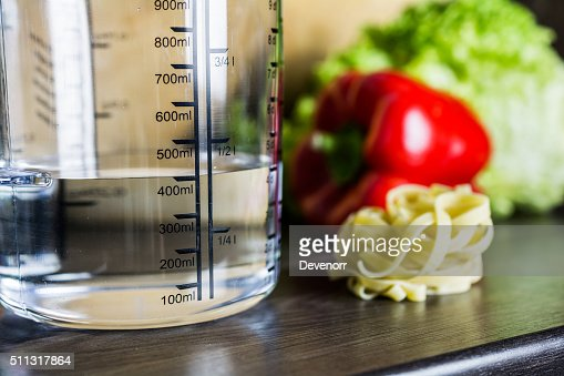 Kitchen Counter With Food 400ml water in measuring cup on kitchen counter with food stock