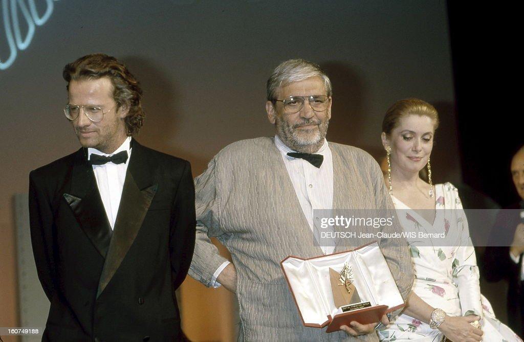 The Closing Ceremony. Catherine DENEUVE et Christophe LAMBERT entourant Maurice PIALAT souriant, sa Palme d'or pour le film 'Sous le soleil de satan' dans la main.