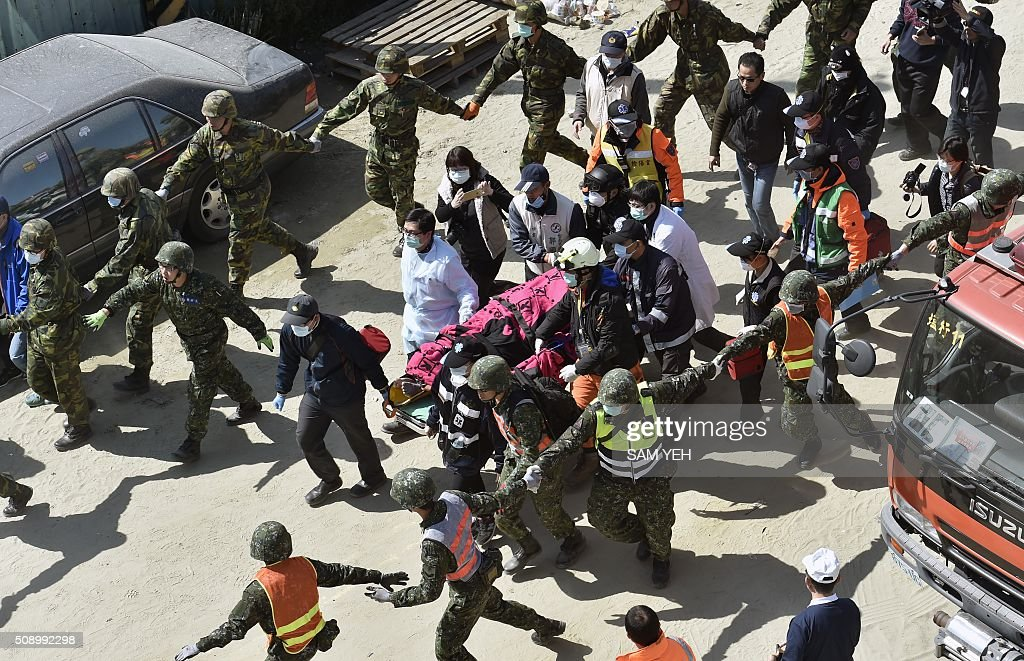 A 40-year-old man (C), identified by local media as Lee Tsung-tian, is transferred by rescue workers after being rescued from the rubble at the Wei-Kuan complex which collapsed in the 6.4 magnitude earthquake, in the southern Taiwanese city of Tainan on February 8, 2016. Two survivors were on February 8 rescued from the rubble of an apartment complex in Taiwan felled by an earthquake, after being trapped for more than 50 hours. AFP PHOTO / Sam Yeh / AFP / SAM YEH