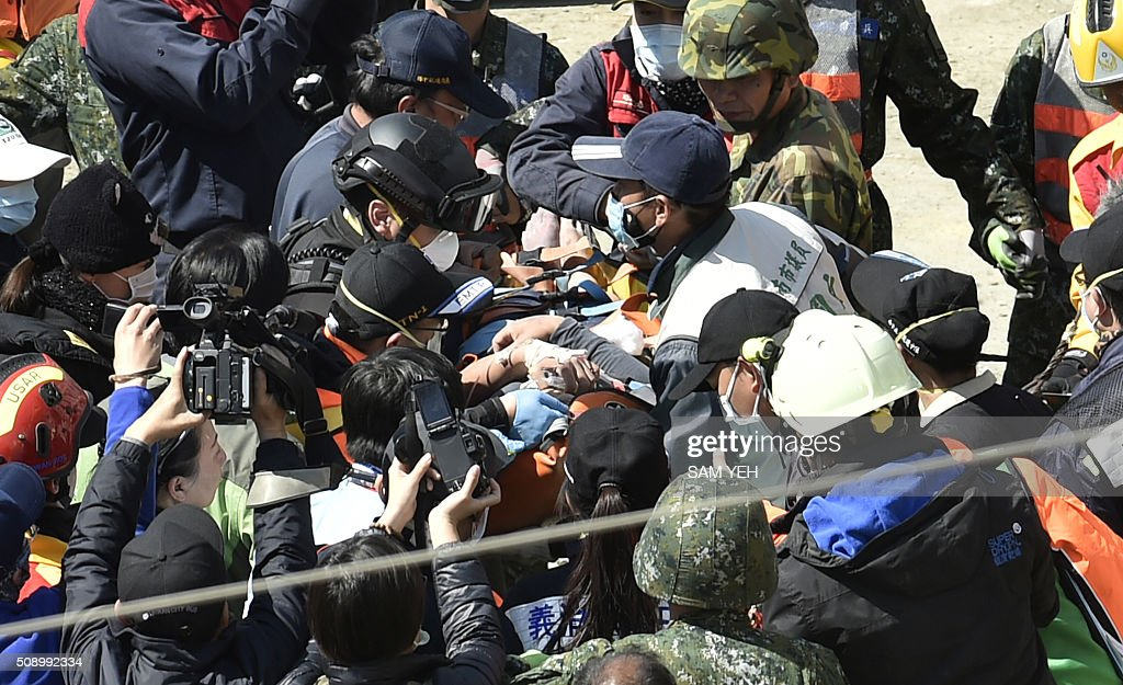 A 40-year-old man (C), identified by local media as Lee Tsung-tian, is checked by medical personnel after being rescued from the rubble at the Wei-Kuan complex which collapsed in the 6.4 magnitude earthquake, in the southern Taiwanese city of Tainan on February 8, 2016. Two survivors were on February 8 rescued from the rubble of an apartment complex in Taiwan felled by an earthquake, after being trapped for more than 50 hours. AFP PHOTO / Sam Yeh / AFP / SAM YEH