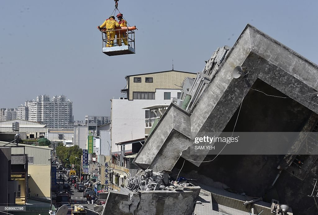 A 40-year-old man, identified by local media as Lee Tsung-tian, is lifted by a crane out of the rubble by rescue workers at the Wei-Kuan complex which collapsed in the 6.4 magnitude earthquake, in the southern Taiwanese city of Tainan on February 8, 2016. Two survivors were on February 8 rescued from the rubble of an apartment complex in Taiwan felled by an earthquake, after being trapped for more than 50 hours. AFP PHOTO / Sam Yeh / AFP / SAM YEH