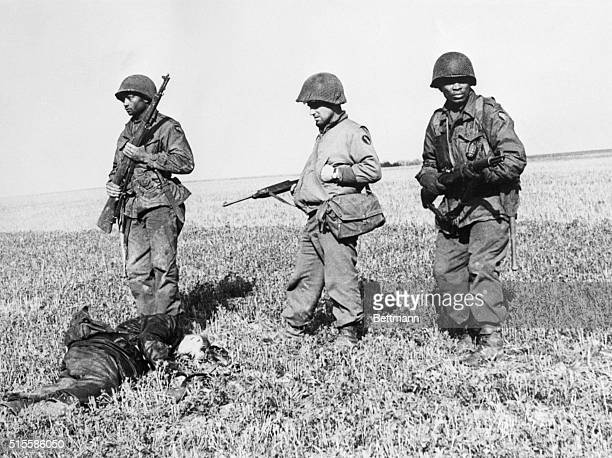 4/17/1945Germany Two Negro infantrymen with their captain all of the 104th First Army Division stand alert while the captain looks over the body of...